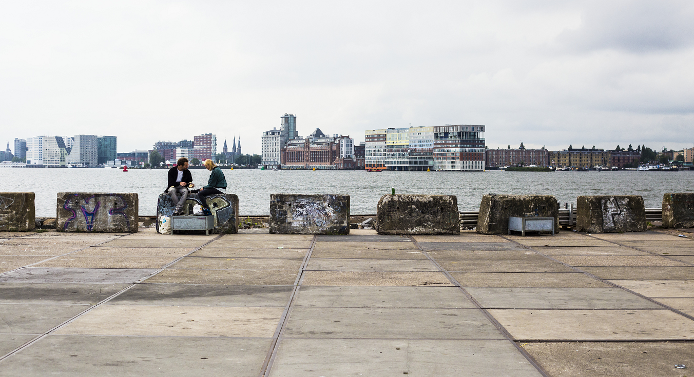 Two people sitting at the docks in Amsterdam.