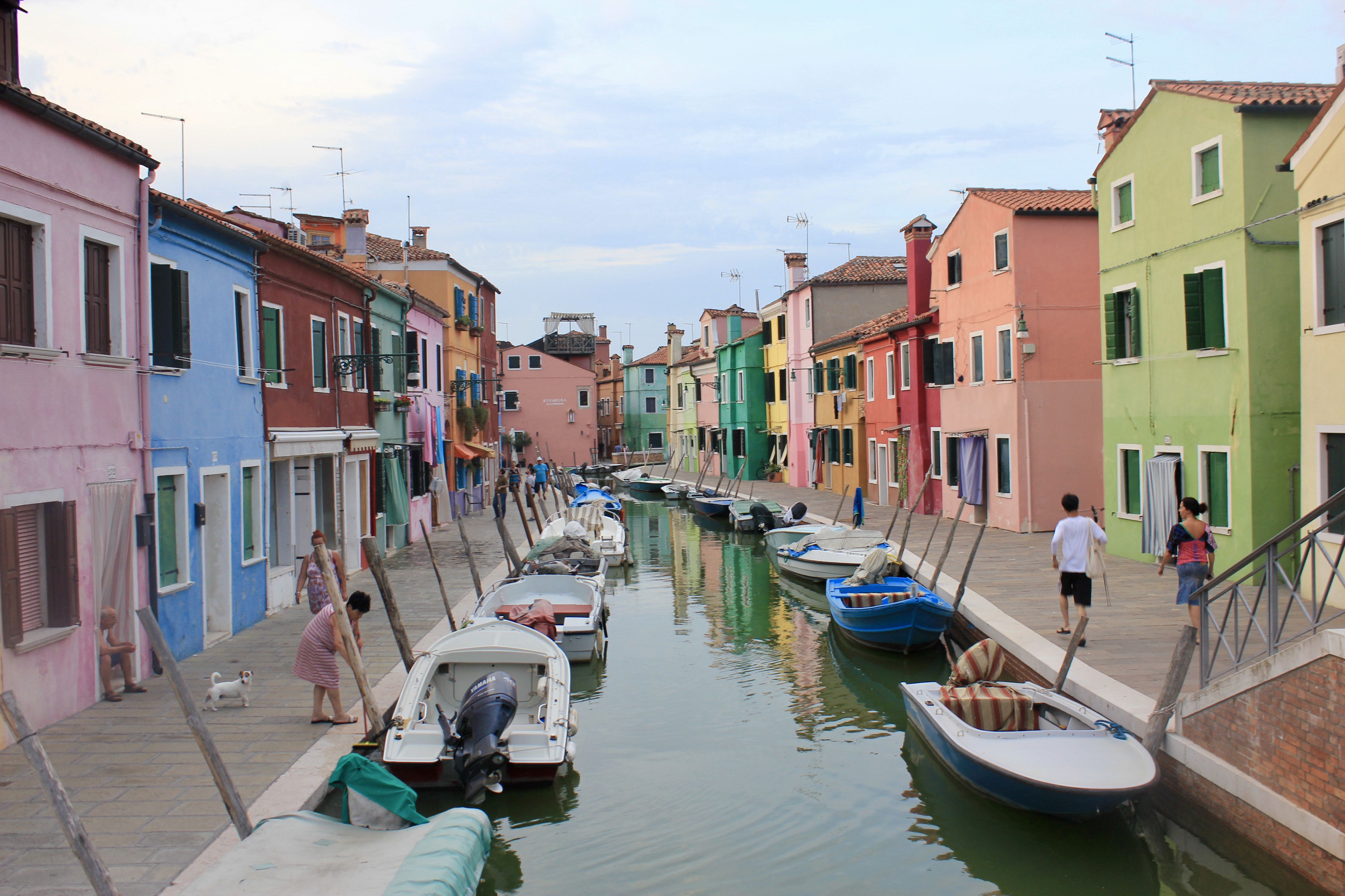 View of pastel-colored houses along a canal lined with small boats in Italy.