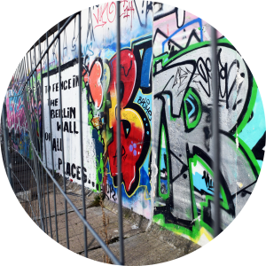 A view of the Berlin wall, with graffiti critiquing the fence around it.