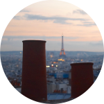 Decorative image with the rooftops of Paris and the Eiffel Tower at sunset, with two small, round chimneys in the foreground.