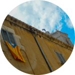 The flag of Catalonia hangs outside a window on a building, with a small statue of an angel visible on the building's cupola, against the sky and clouds above.