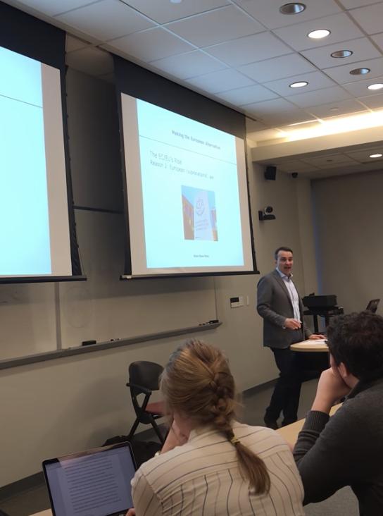 Kiran Klaus Patel speaks in front of a PowerPoint presentation.