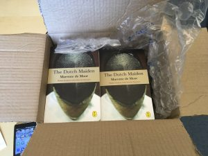 A box with packing material, open to show two stacks of books, with their covers facing upward.