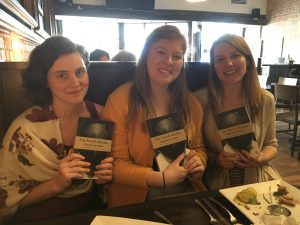 Three women sit together in a cafe booth, smiling and each holding up one book, the cover facing the photographer.