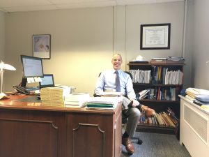 Professor sitting at desk with books.
