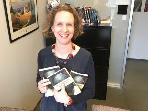 Katie stands smiling holding three books fanned out.