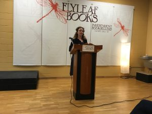 The author speaks, standing at a podium at the front of a room, with the Flyleaf Books logo on the wall behind her.