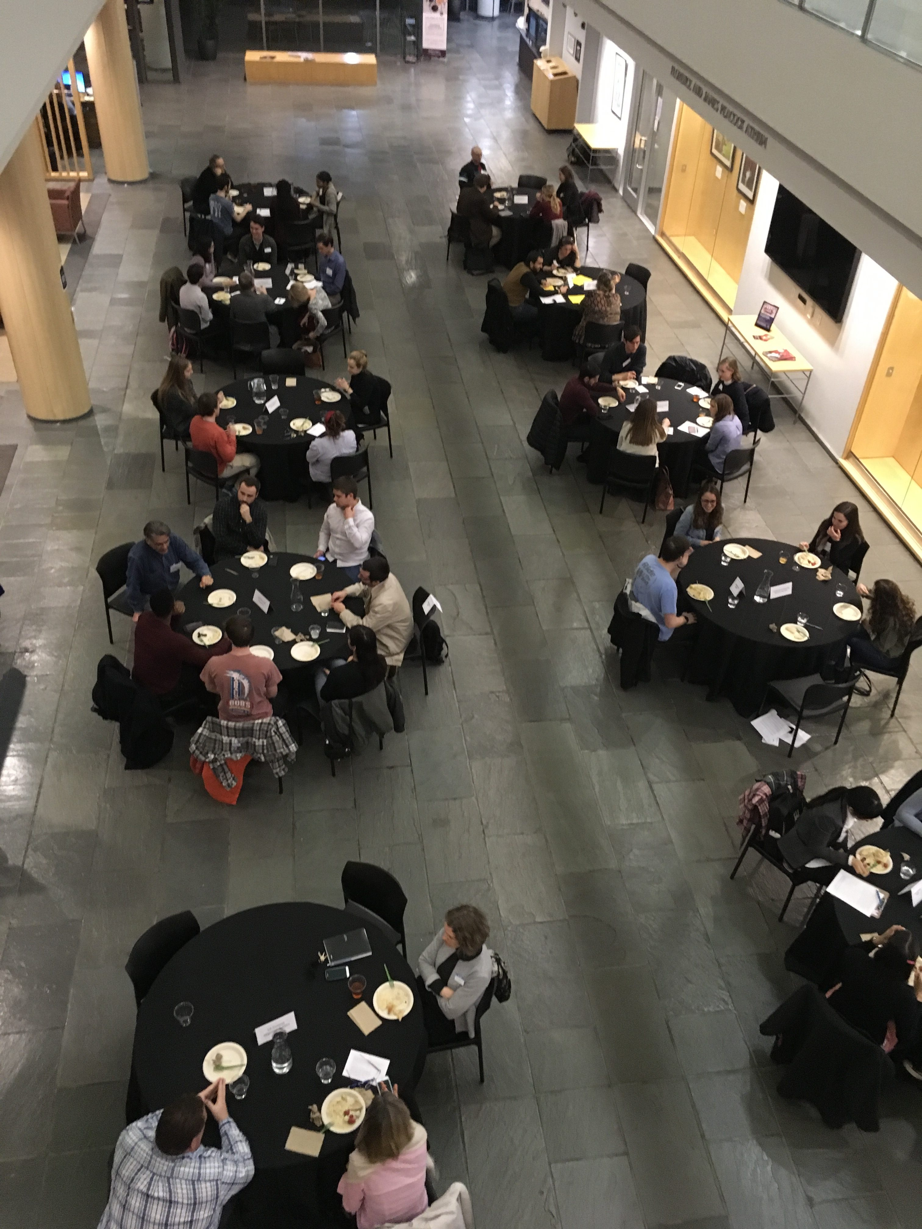 People sitting down at tables and eating in the atrium of the Global Education Center.