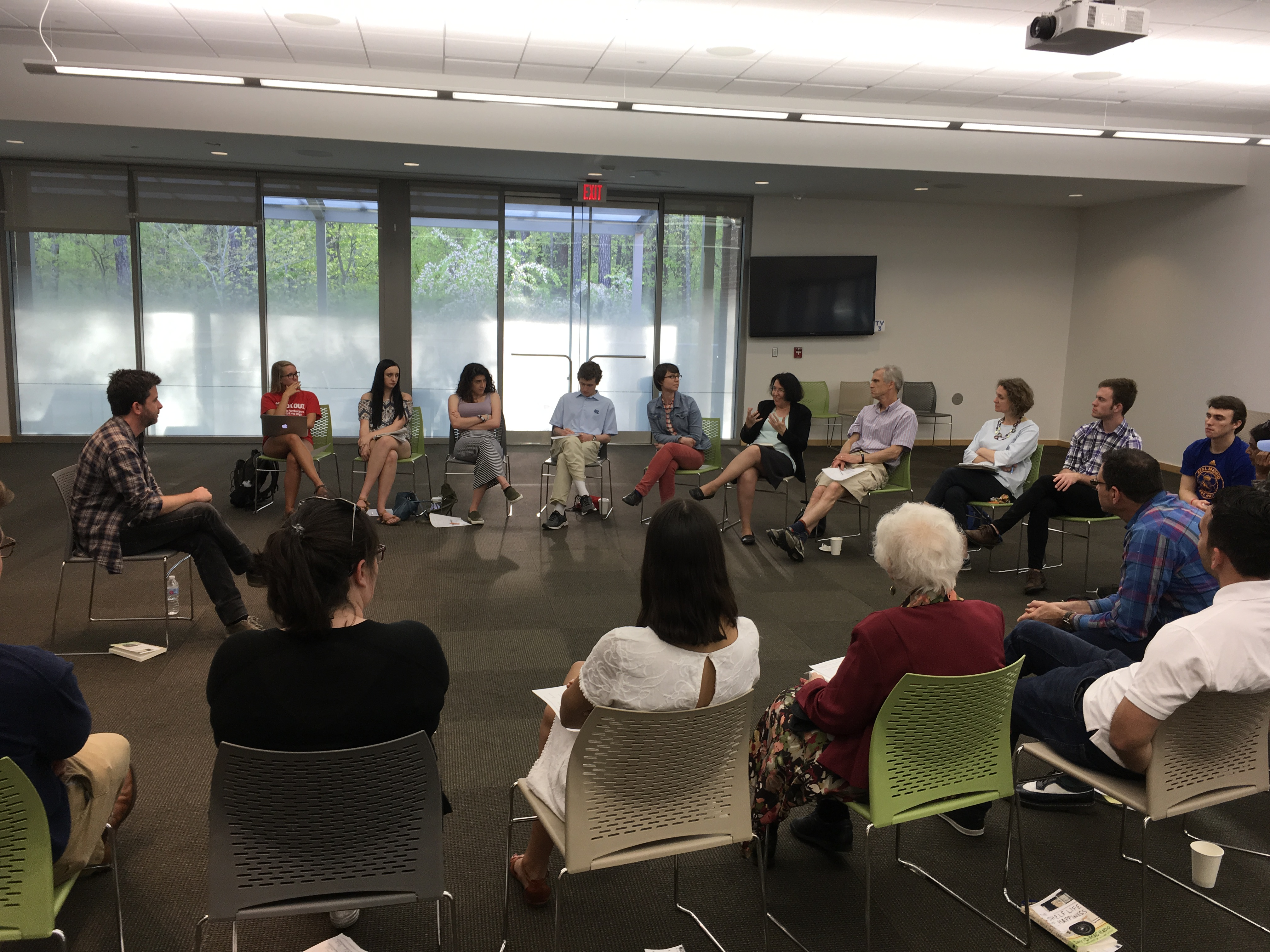 Author David Machado sits in front of a semicircle of chairs with people sitting in them at a room at the local library.