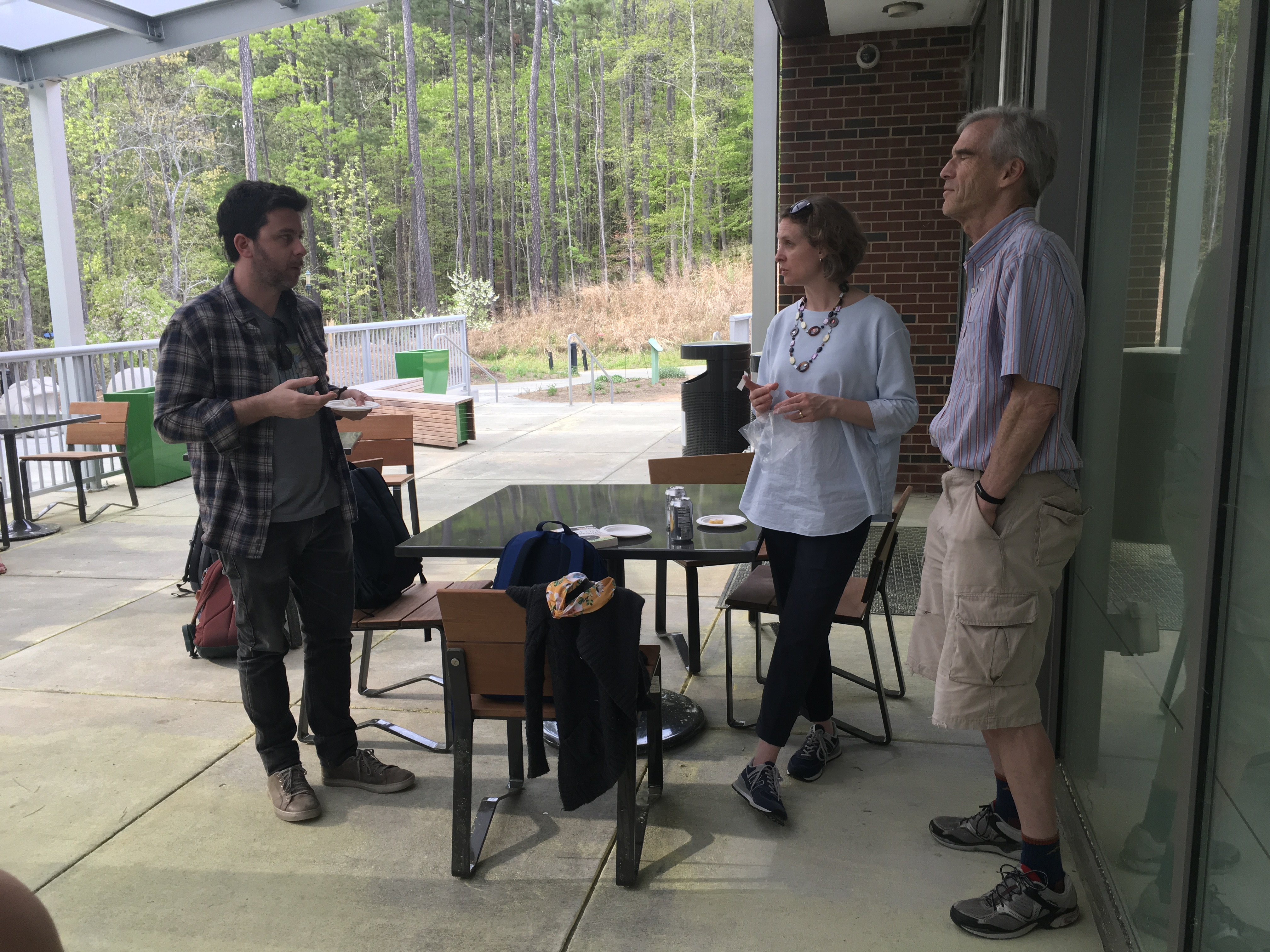 Author David Machado talks to UNC staff on a patio with trees behind him.