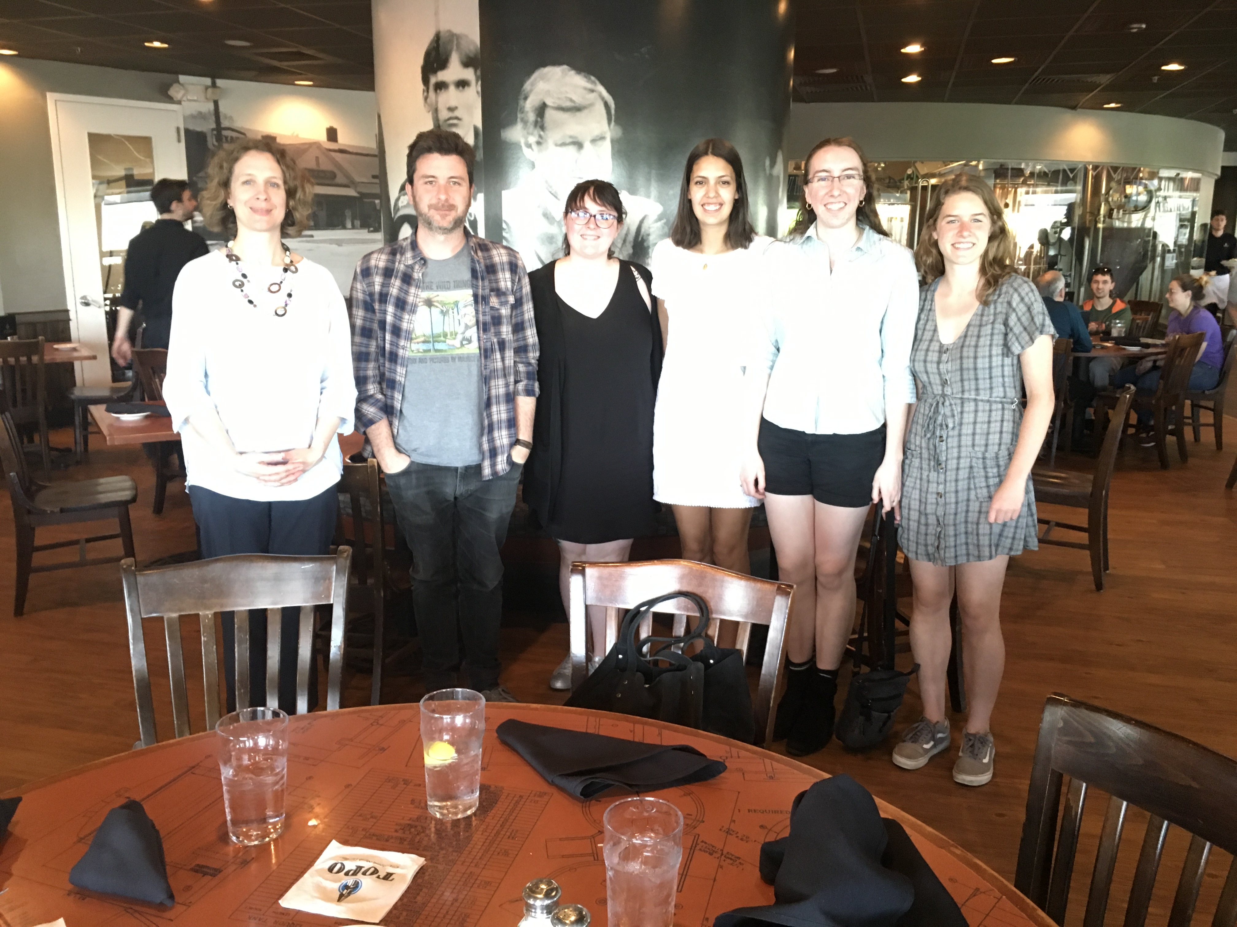 Author David Machado stands in a line of UNC staff and students smiling at the camera at a local restaurant.