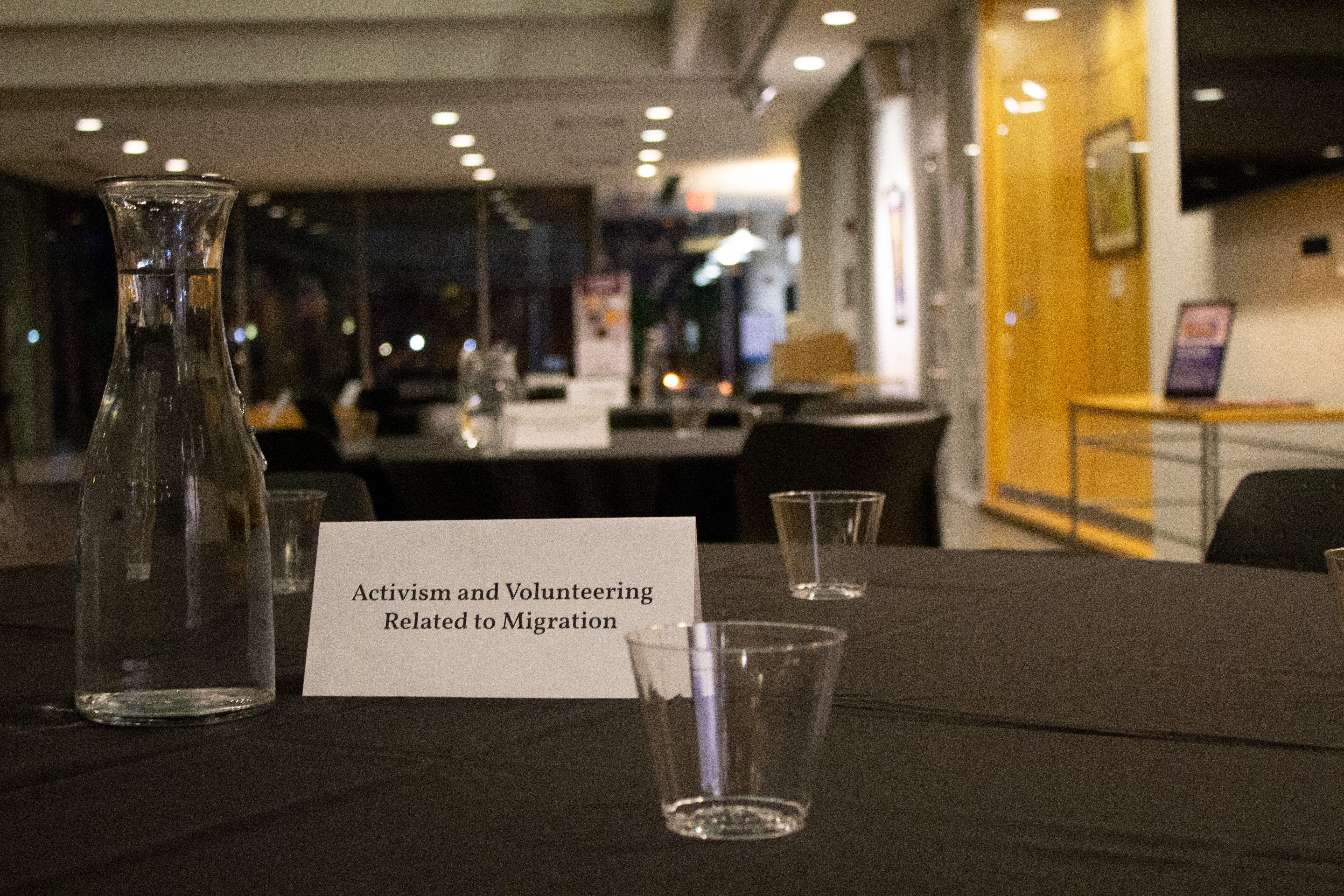 A round table with a sign that says activism and volunteering related to migration.