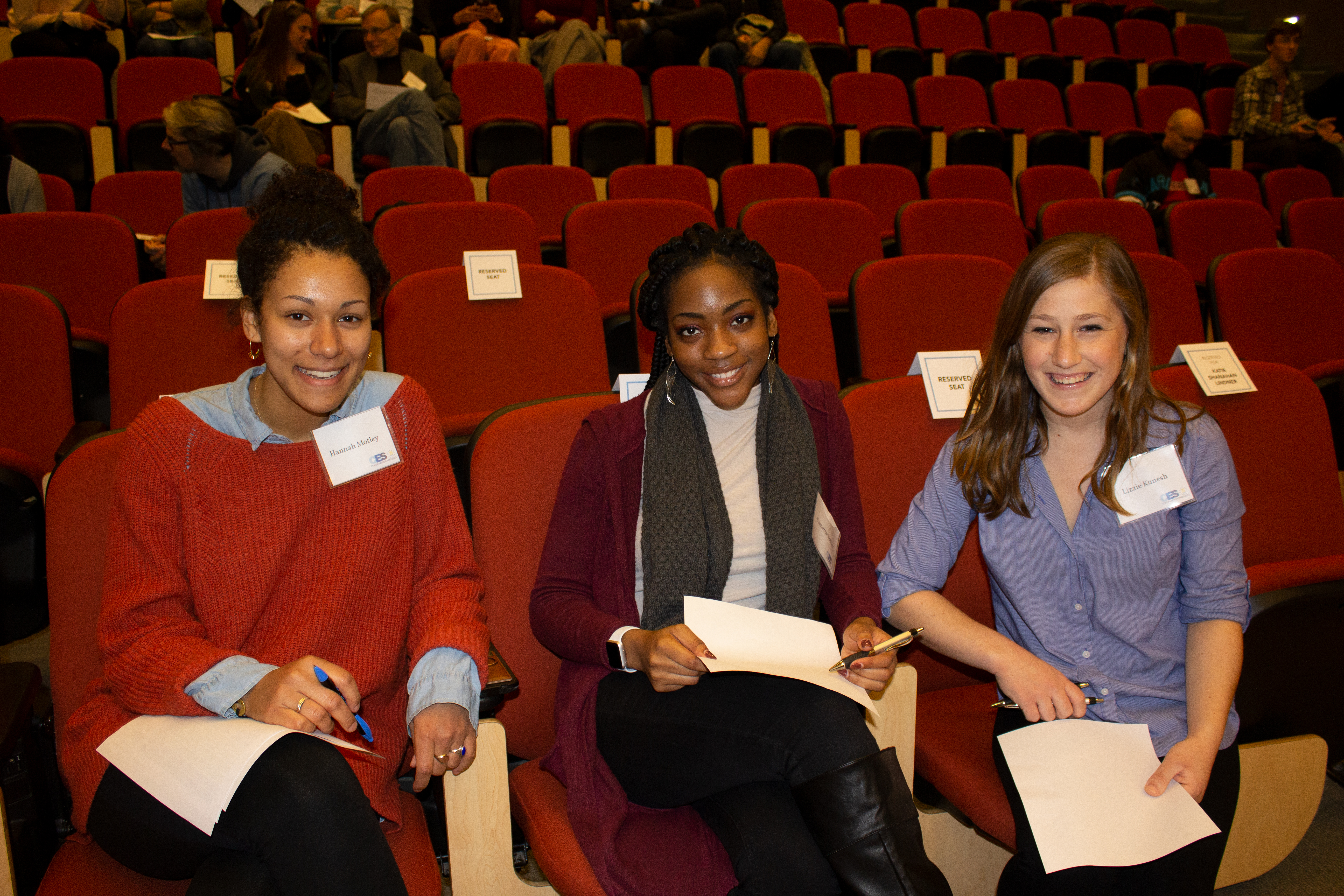 Three women sit in the front row of the auditorium holding paper and pens and smiling at the camera.
