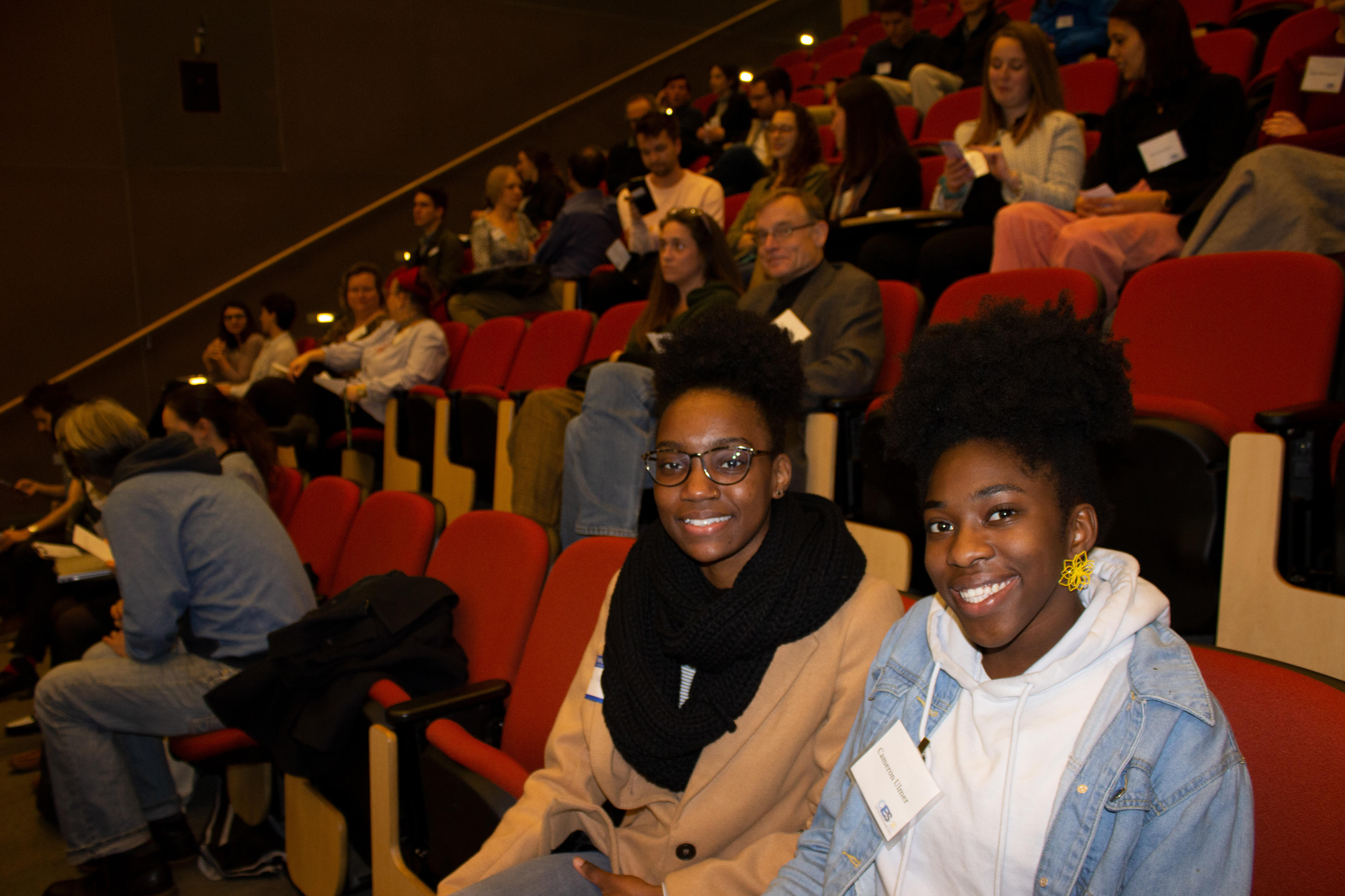 Two women sit in the front row of an auditorium and smile at the camera.