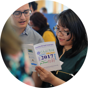 Two students read over a brochure that says Learning Through Languages 2017.