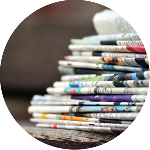 Stack of newspapers sit on a table.