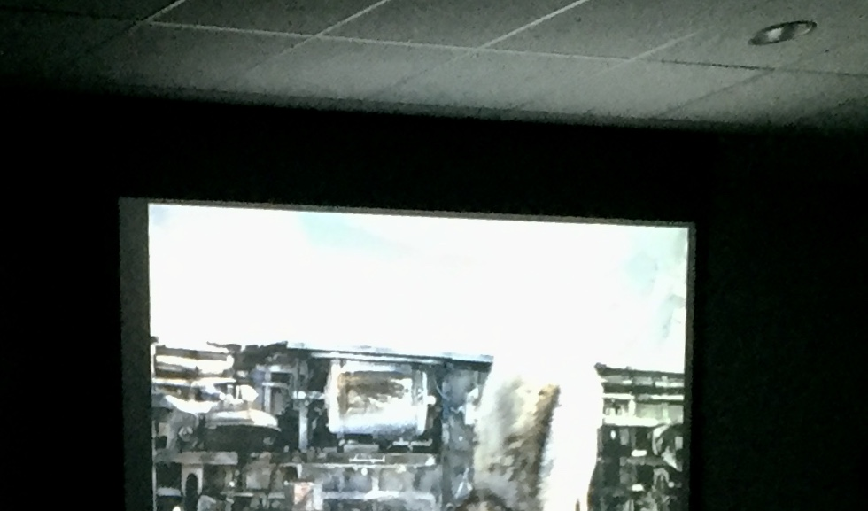 A scene from Snowpiercer is projected onto a screen in a dark classroom.