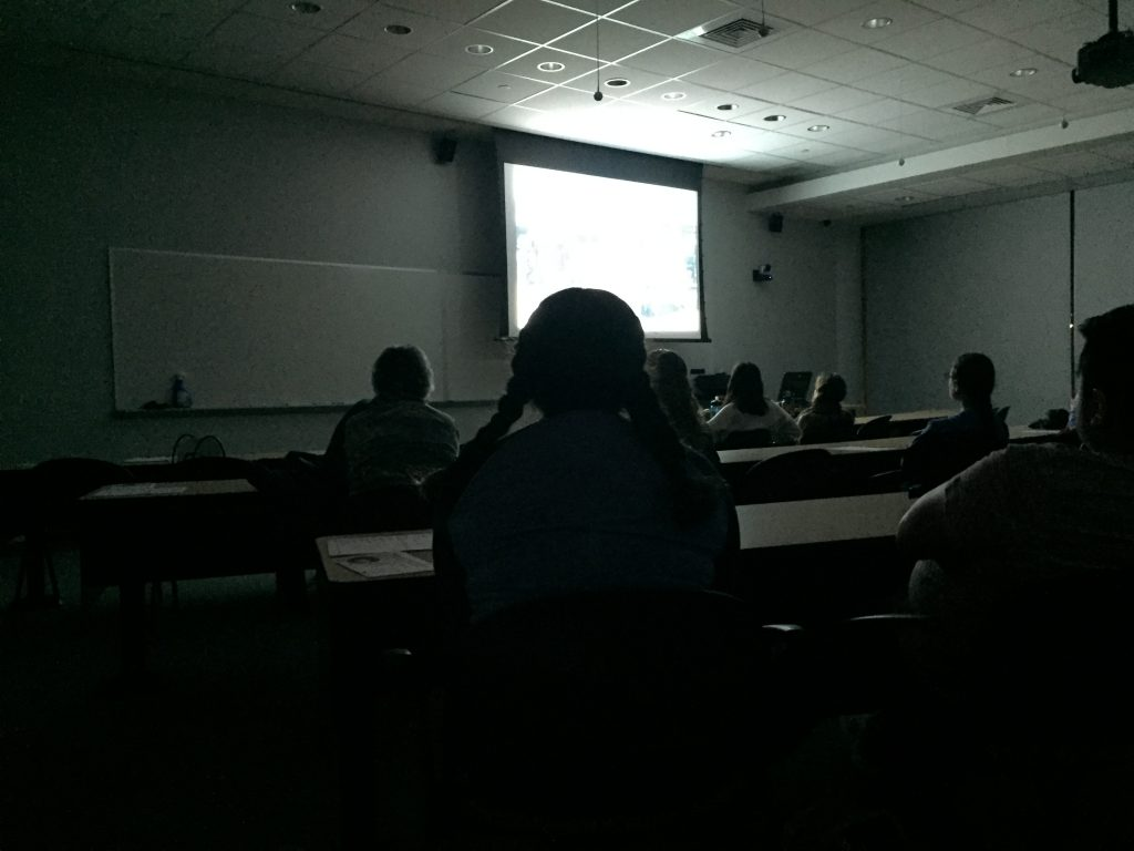 A scene from Snowpiercer is projected onto a screen in a dark classroom with silhouettes of event attendees in the foreground.