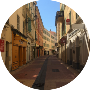 A narrow pedestrian street bathed in sunlight with blue sky in the background.